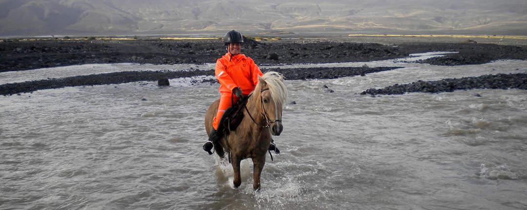 Rider på islandshäst över älven Markarfljót