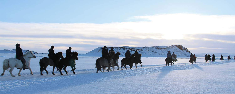 Rider islandshäst på frusna sjöar på Island