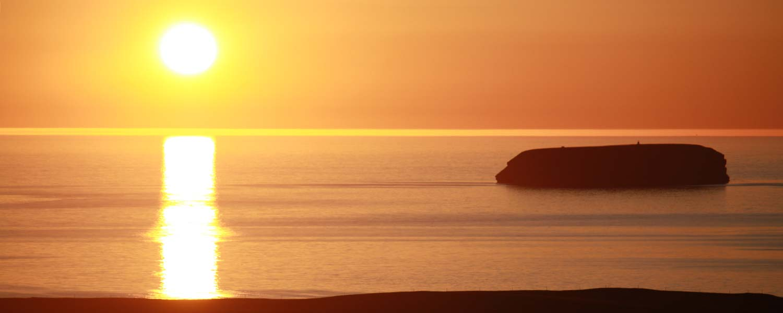 Rider med vy över den blodröda solen som svävar över det glittrande havet under natten