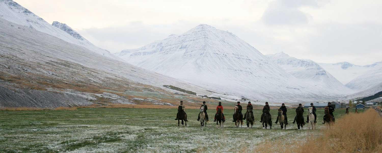 Rider på islandshäst med magisk vi i bakgrunden av snötäckta berg på Island