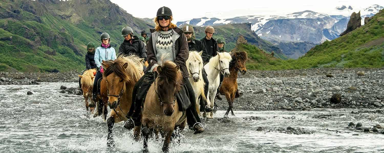 Ridsällskapet passerar en bäck med mäktiga berg i bakgrunden