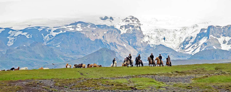 Ridera på islandshäst med glaciärerna Myrdalsjökull och Eyjafjallajökull i bakgrunden