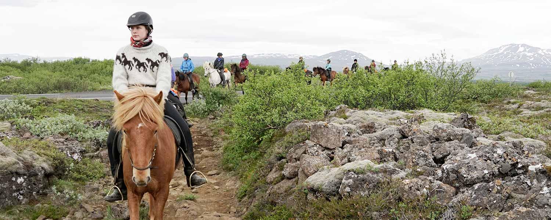 Rider på islandshäst i nationalparken Thingvellir på Island