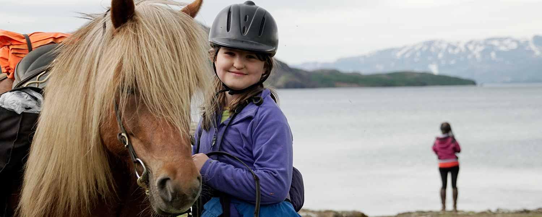 Ridpaus med islandshäst och barn vid sjön Thingvallavatn