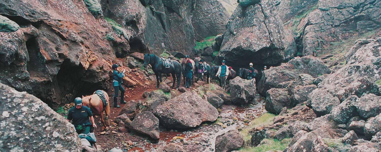 Rider genom den trånga klyftan till Marardalur, hästarnas dal på Island