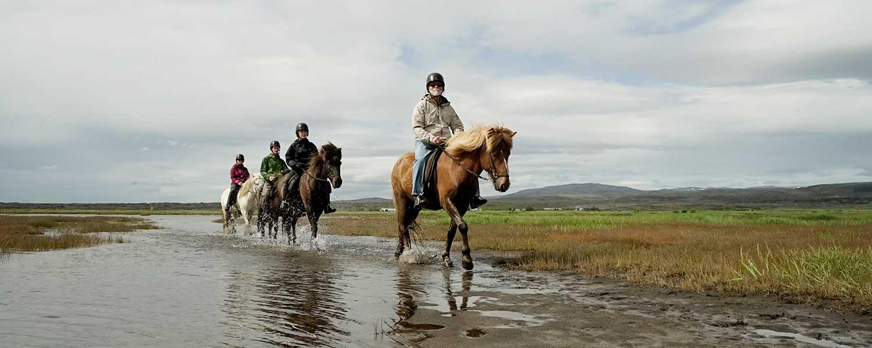 Rider genom grunt vatten med lavasand