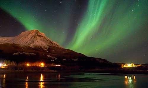 Norrsken som sveper förbi vacker berg på Island