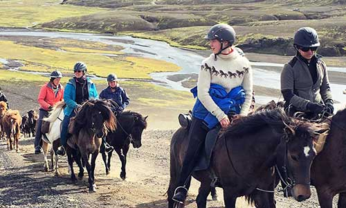Ridsällskap rider uppför kulle med vackra vyer på Island