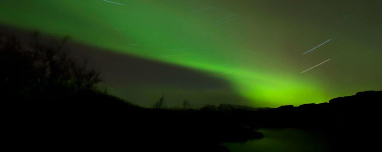 Isländsk natthimmel som lyser av stjärnor och dansande norrsken Aurora Borealis